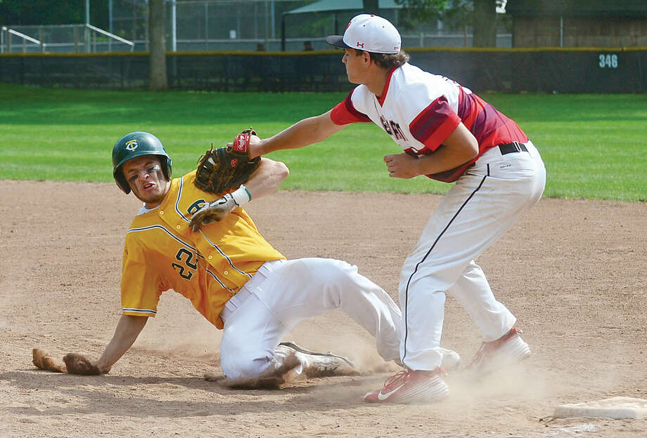Hour photo / Erik Trautmann Trinity Catholic's #22 Anthony Hoegemann gets doubled up at first by New Canaan's first baseman Robby Jones during their FCIAC semi final Tuesday at Mead Park in New Canaan.