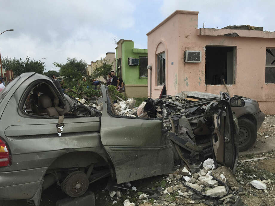 """People stand near a destroyed vehicle after a powerful tornado swept past in Ciudad Acuna, northern Mexico, Monday, May 25, 2015. A tornado raged through the city on the U.S.-Mexico border Monday, destroying homes and flinging cars like matchsticks. At least 13 people were killed, authorities said. The twister hit a seven-block area, which Victor Zamora, interior secretary of the northern state of Coahuila, described as """"devastated."""" (AP Photo)"""