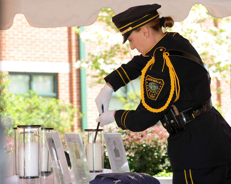 Detective Kristina LaPak lights the candles for the four fallen officers during the annual Norwalk Police Department Memorial on Wednesday, May 18, 2016 at police headquarters in Norwalk, Conn. The service was held as part of national police week to honor the memory of fellow officers who have lost their lives in the service as well as those lost to suicide.