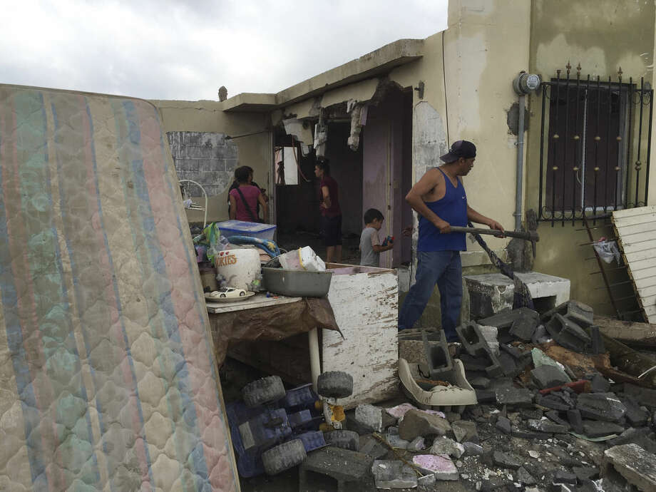 """Residents clear away debris from their home after a powerful tornado swept past in Ciudad Acuna, northern Mexico, Monday, May 25, 2015. A tornado raged through the city on the U.S.-Mexico border Monday, destroying homes and flinging cars like matchsticks. At least 13 people were killed, authorities said. The twister hit a seven-block area, which Victor Zamora, interior secretary of the northern state of Coahuila, described as """"devastated."""" (AP Photo)"""