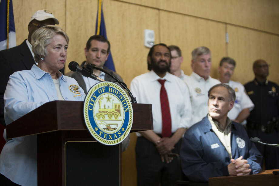 Houston Mayor Annise Parker, left, accompanied by Texas Gov. Greg Abbott, right, addresses the damage and recovery efforts after destructive area storms, Tuesday, May 26, 2015, in Houston. Floodwaters kept rising Tuesday across much of Texas as storms dumped almost another foot of rain on the Houston area, stranding hundreds of motorists and inundating the famously congested highways that serve the nation's fourth-largest city. (Marie D. De Jesus/Houston Chronicle via AP)