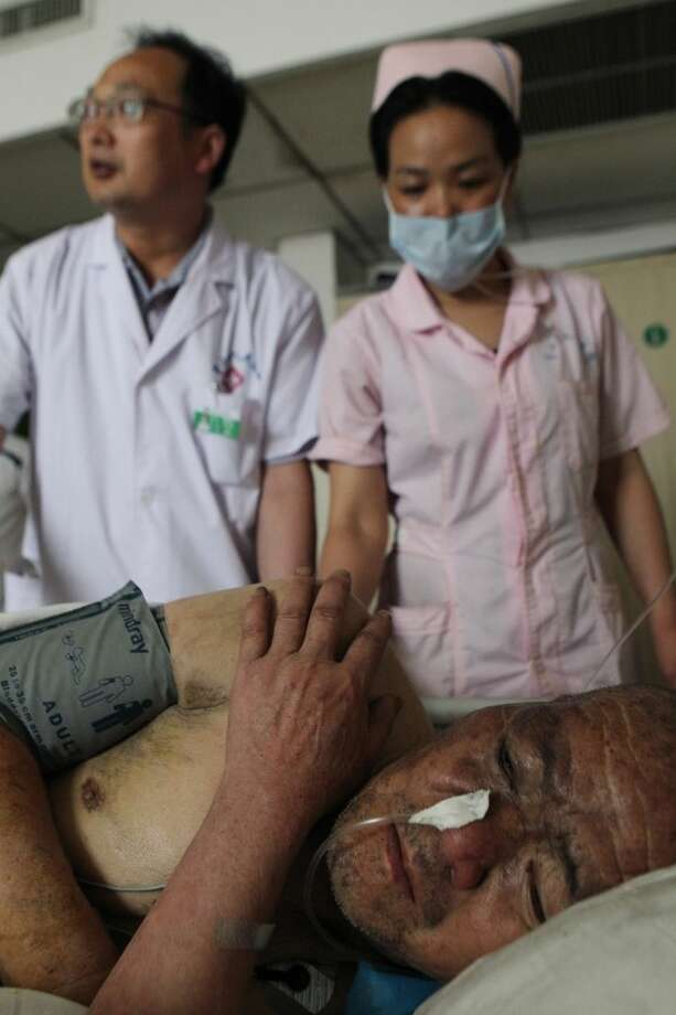 In this photo released by China's Xinhua News Agency, Wu Zhongfeng, an man injured in a fire, receives treatment at a hospital in Pingdingshan, central China's Henan Province Tuesday, May 26, 2015. A fire swept through a rest home in central China, killing more than 35 people and injuring several, Chinese authorities said Tuesday. The fire broke out Monday night in an apartment building being used as a privately run rest home in the city of Pingdingshan in Henan province, according to a statement from the province's work safety administration. (Xinhua via AP) NO SALES