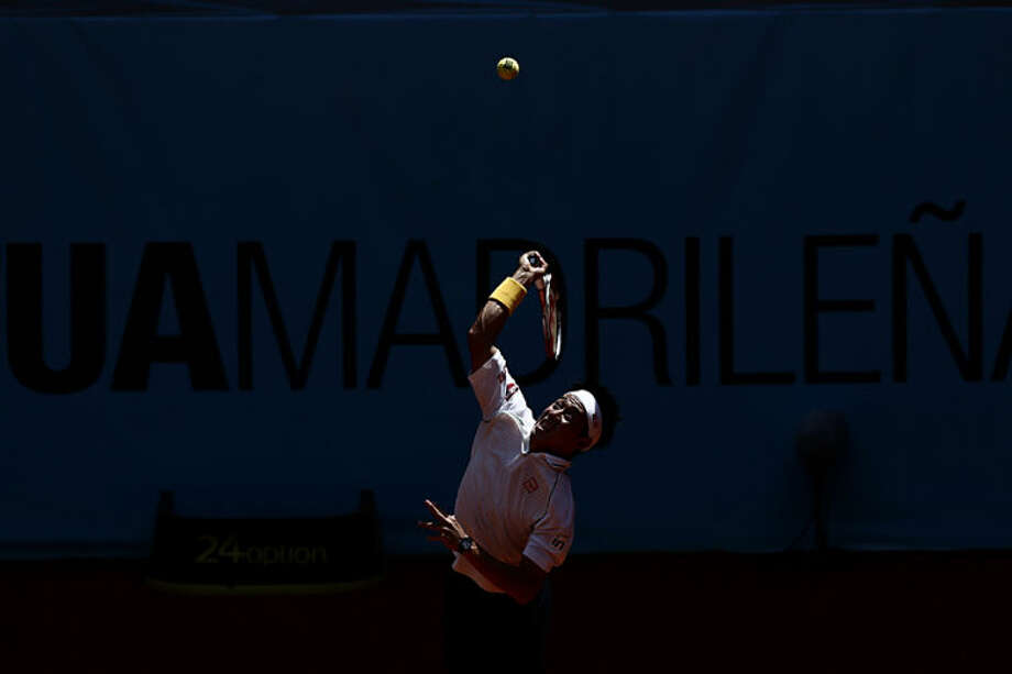 Kei Nishikori from Japan serves the ball during a Madrid Open tennis tournament match against Milos Raonic from Canada in Madrid, Spain, Thursday, May 8, 2014 . (AP Photo/Daniel Ochoa de Olza)