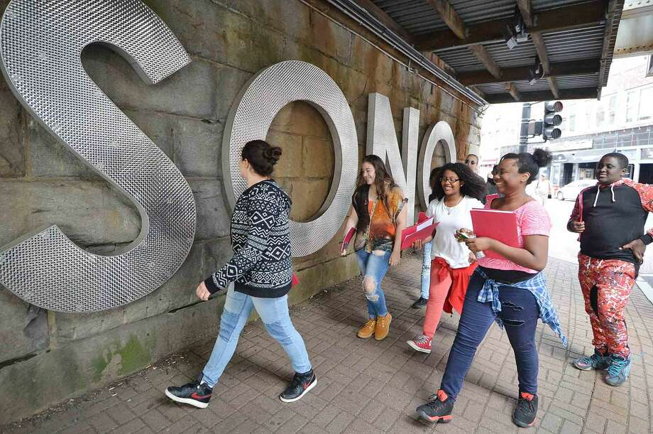 Students with the Norwalk Housing Authority 20 West Arts program walk under the railroad bridge next to the SONO sign at the corner of Washington St. and So. Main. The students are learning to be tour guides for the SONO Public Walking Tour on June 11