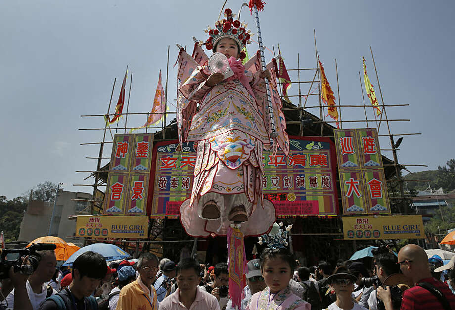 A girl dressed in the traditional Chinese costume floats in the air, supported by a rig of hidden metal rods, during a parade on the outlying Cheung Chau island in Hong Kong Monday, May 25, 2015 to celebrate the Bun Festival. The festival is held every year to placate the spirits of people killed by pirates. (AP Photo/Vincent Yu)