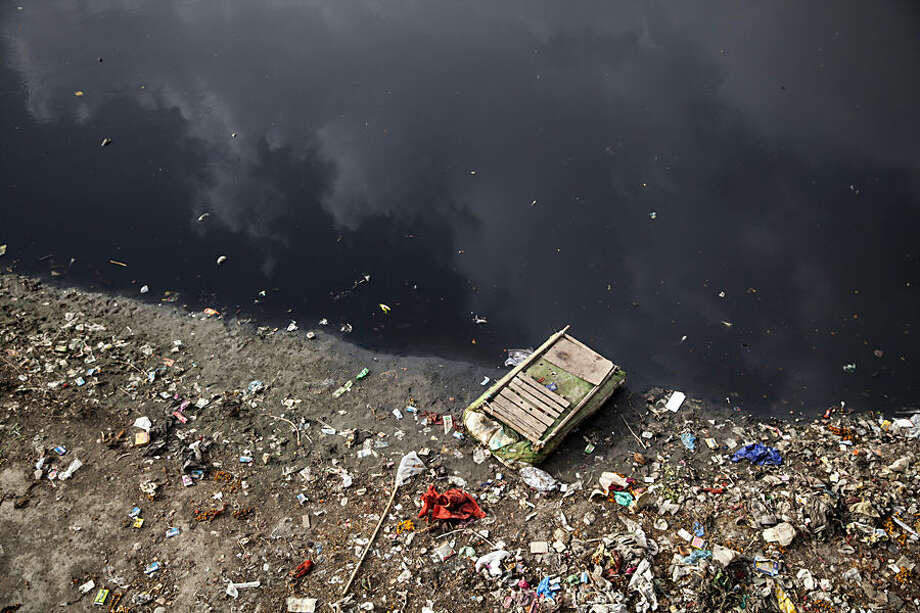 In this Monday, May 25, 2015, photo, a raft lies on the polluted banks of the River Yumuna in New Delhi, India. Indian prime minister Narendra Modi's first year in office was punctuated with promises of clear rivers, clean energy and toilets for all, but environmentalists worry his government is on an entirely different path: dismantling hard-won environmental laws in the name of boosting growth. (AP Photo/Tsering Topgyal)