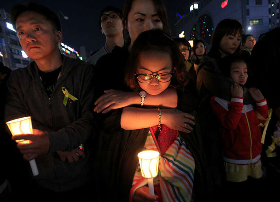 A girl holds a candle during a rally to pay tribute to the victims and missing passengers of the sunken ferry Sewol, in Ansan, South Korea, Friday, May 9, 2014. South Korean prosecutors are seeking to formally arrest the head of the company that owns the doomed ferry in part of their investigation into its sinking last month that left more than 300 people, mostly high school students, dead or missing, officials said Friday. (AP Photo/Ahn Young-joon)
