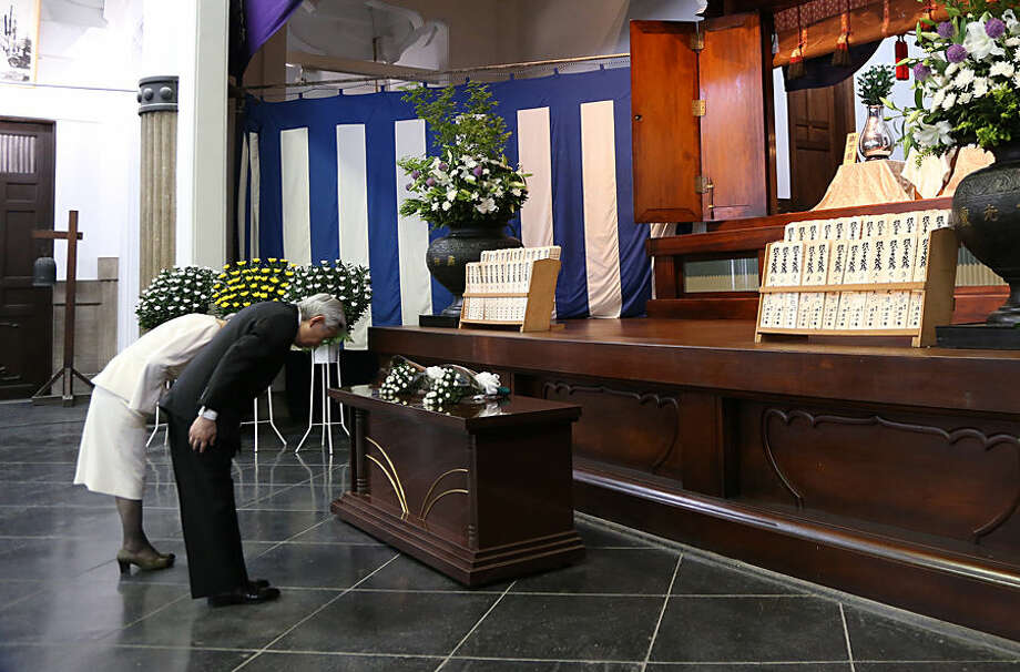 Japan's Emperor Akihito, right, and Empress Michiko bow deeply after offering flowers during a memorial service for the victims of the 1923 Great Kanto earthquake and the 1945 firebombings in Tokyo at Tokyo Memorial Hall Tuesday, May 26, 2015, marking the 70th anniversary of the end of World War II. (AP Photo/Eugene Hoshiko, Pool)