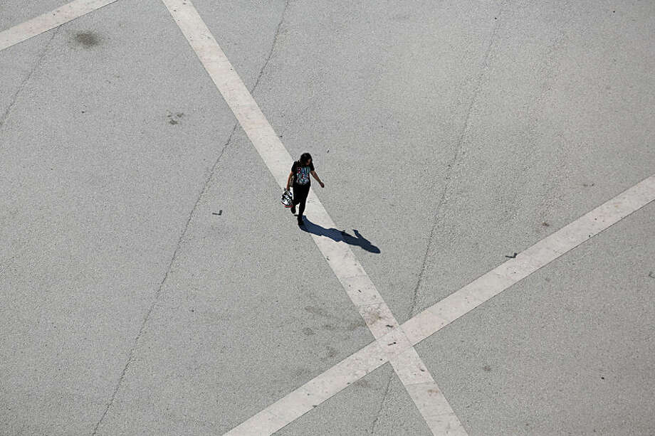 A woman casts a shadow while walking across Comercio Square in Lisbon Tuesday, May 26, 2015. The monumental square used to be home to the Portuguese royal family's palace until 1755 when it was flattened by a massive earthquake. (AP Photo/Armando Franca)