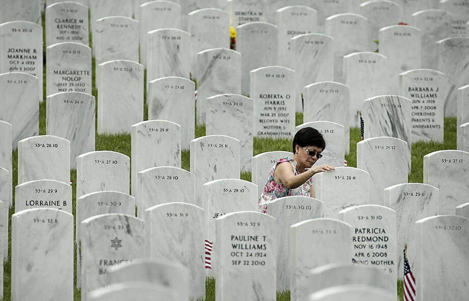 Ester Grod puts her hand on her husband's gravestone at the Leavenworth National Cemetery on Memorial Day, Monday, May 25, 2015, in Leavenworth, Kan. (AP Photo/Charlie Riedel)