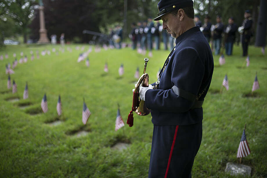 Peter Sturvedant, dressed in Civil War era attire, prepares to play taps during a Memorial Day ceremony in honor of soldiers who died in the Civil War, Monday, May 25, 2015, at Spring Grove Cemetery in Cincinnati. The cemetery is the final resting place of around 6,000 soldiers. (AP Photo/John Minchillo)