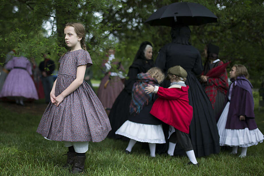 Bria Lee, of Milford, Ohio, wears Civil War era clothing during a Memorial Day ceremony, Monday, May 25, 2015, at Spring Grove Cemetery in Cincinnati. Lee attended with the Ladies Living History Society, who all wore period-specific attire. (AP Photo/John Minchillo)