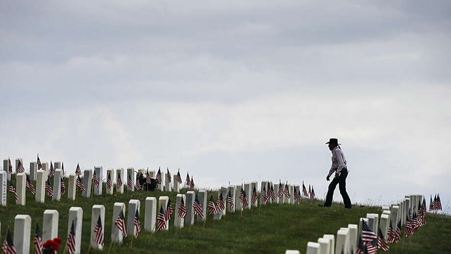 Newton Old Crow Sr., of Lodge Grass, Mont., walks a ridge line amongst the many graves at Little Bighorn National Cemetery near Crow Agency, Mont., on Memorial Day, Monday, May 25, 2015. Old Crow is a Army veteran and has two sisters buried at the cemetery. (Travis Heying/The Wichita Eagle via AP) LOCAL TELEVISION OUT; MAGS OUT; LOCAL RADIO OUT; LOCAL INTERNET OUT