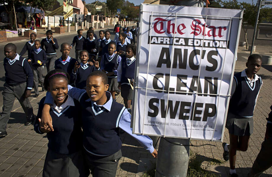 Schoolchildren walk past a newspaper placard reporting the election victory of Jacob Zuma's African National Congress (ANC) party, based on preliminary results, as the children leave after making a visit to the former house of the late South African President Nelson Mandela, in the Soweto township of Johannesburg, South Africa Friday, May 9, 2014. Vote-counting in elections in South Africa is almost complete, indicating a comfortable win for the ruling African National Congress but also a strengthening of key opposition rivals that promised change after 20 years of leadership by the party that led the fight against apartheid. (AP Photo/Ben Curtis)