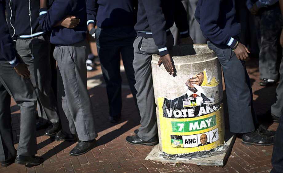 Schoolchildren who had just paid a visit to the former house of the late South African President Nelson Mandela, stand by a partially-ripped election poster of Jacob Zuma's African National Congress (ANC) party in the Soweto township of Johannesburg, South Africa Friday, May 9, 2014. Vote-counting in elections in South Africa is almost complete, indicating a comfortable win for the ruling African National Congress but also a strengthening of key opposition rivals that promised change after 20 years of leadership by the party that led the fight against apartheid. (AP Photo/Ben Curtis)
