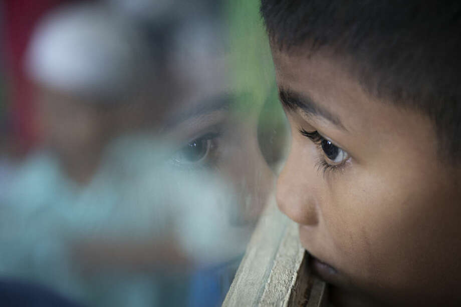 In this May 21, 2015 photo, Sadhussin Mohamad, 6, a Rohingya schoolboy, watches teacher day celebrations outside his classroom at a Rohingya Education Center in Klang, Malaysia. With more work opportunities than Indonesia and a more Muslim-friendly environment than Thailand, Malaysia has long been the destination of choice for Rohingya Muslims fleeing persecution in Myanmar. (AP Photo/Vincent Thian)