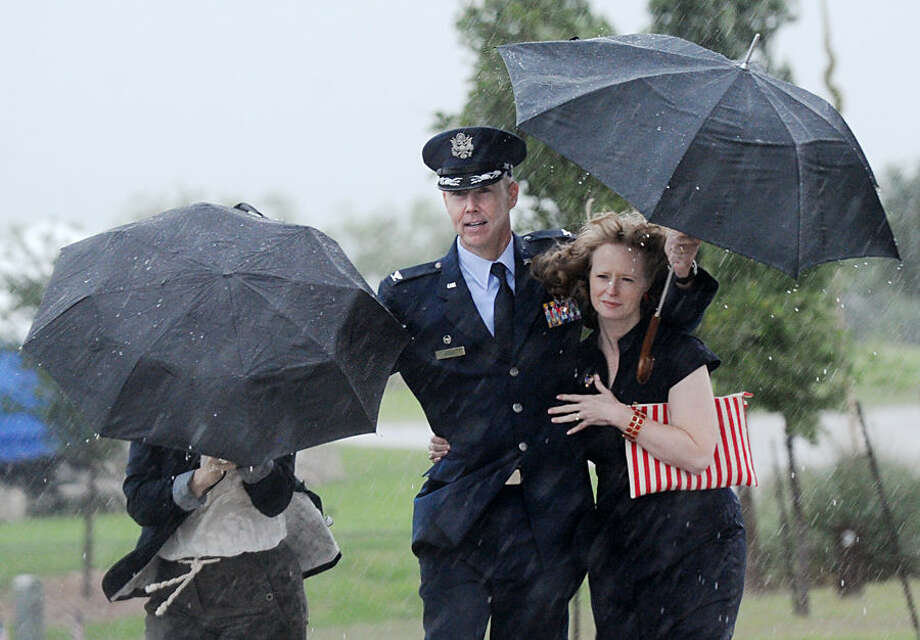 Memorial Day commemoration attendees leave after heavy rain caused the event to be canceled at the Texas State Veterans Cemetery, Monday, May 25, 2015, in Abilene, Texas. (Nellie Doneva/The Abilene Reporter-News via AP)