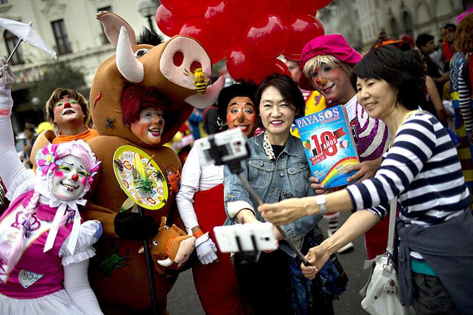 Tourist Gina Youginkim, right, and Margaret Kahng, from South Korea, third from right, pose for a picture with clowns during a march commemorating the Peruvian clown day in Lima Peru, Monday, May 25, 2015. Hundreds of professional clowns dressed in colorful costumes, wigs and face paint marched through the streets of Lima to celebrate Peruvian Clown Day. (AP Photo/Rodrigo Abd)