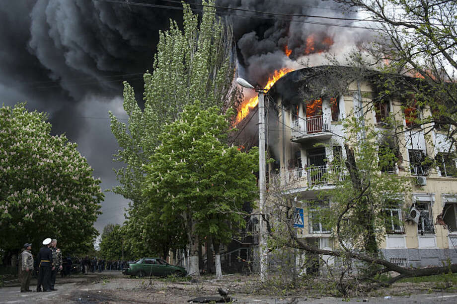 A police station is ablaze in Mariupol, eastern Ukraine, Friday May 9, 2014. Fighting between government forces and insurgents in Mariupol has left several people dead. (AP Photo/Evgeniy Maloletka)