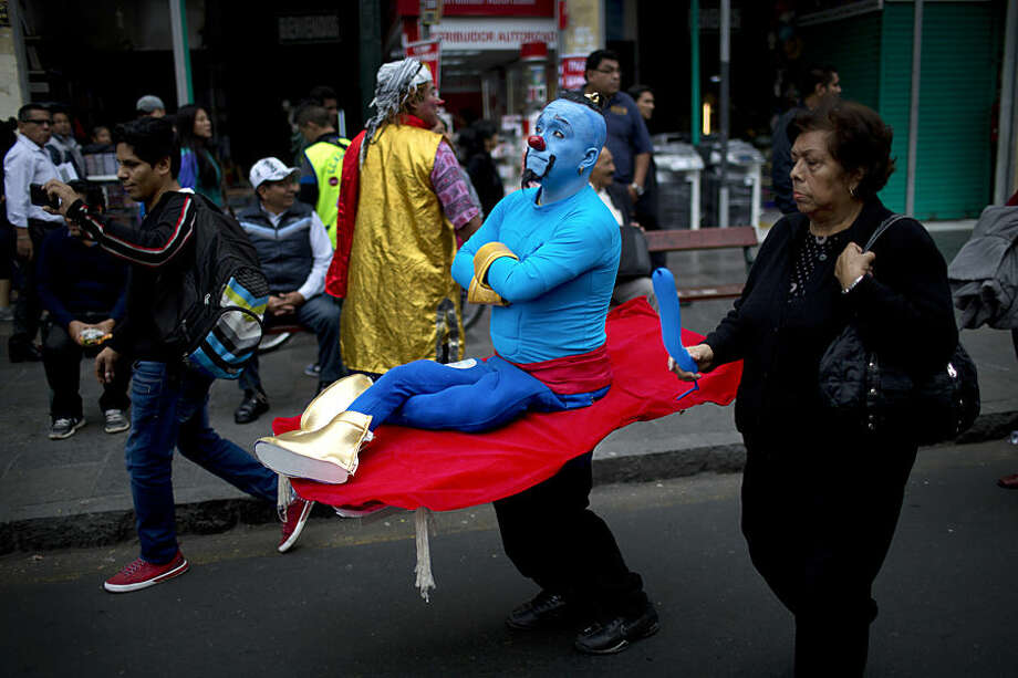 A clown marches while commemorating the Peruvian clown day in Lima Peru, Monday, May 25, 2015. Hundreds of professional clowns dressed in colorful costumes, wigs and face paint marched through the streets of Lima to celebrate Peruvian Clown Day. (AP Photo/Rodrigo Abd)