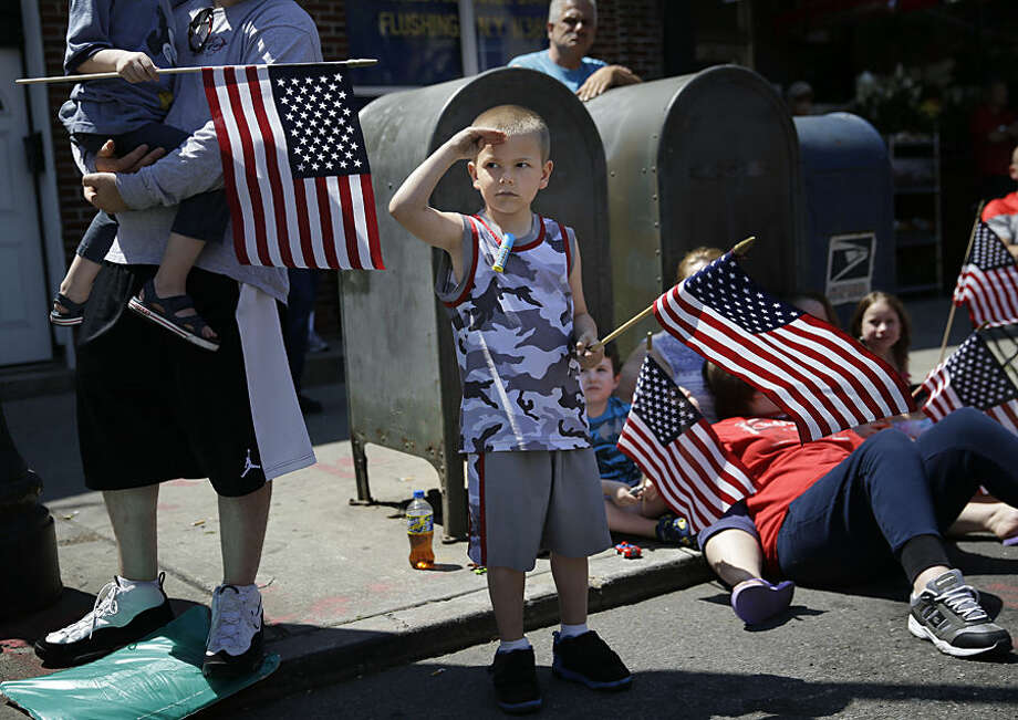 Rocco Struncius salutes as soldiers walk by during a Memorial Day parade in the Glenwood neighborhood of New York, Monday, May 25, 2015. President Barack Obama saluted Americans who died in battle Monday, noting the first Memorial Day in 14 years without U.S. forces involved in a major ground war. (AP Photo/Seth Wenig)