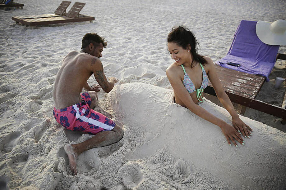 In this Wednesday, May 13, 2015 photo, Demarkis Mosley, left, and his wife, Alexandria, of Starkville, Miss., play in the sand on their vacation in Gulf Shores, Ala. Industry officials say Gulf Coast tourism is surging, five years after the BP oil spill. (AP Photo/Brynn Anderson)