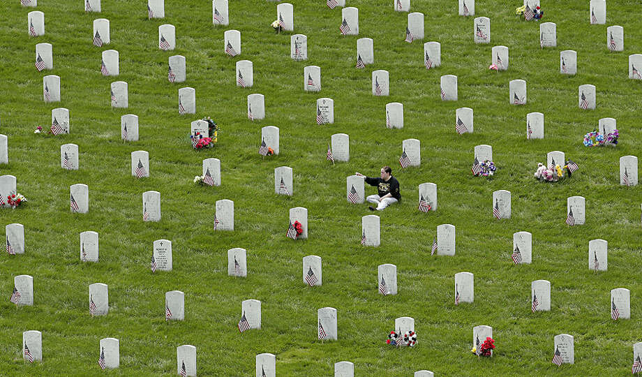 A woman sits by a grave as she observes Memorial Day at the Leavenworth National Cemetery, Monday, May 25, 2015, in Leavenworth, Kan. (AP Photo/Charlie Riedel)