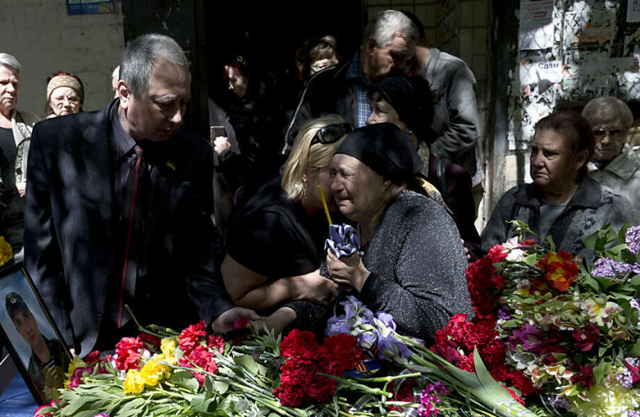 The mother of Dmitriy Nikityuk, a Cossack, holds a candle while crying next to his coffin during the funeral in Odessa, Ukraine, Thursday, May 8, 2014. Nikityuk died of gas poisoning in the burning trade union building fire that killed most of the 40 people that died after riots erupted last Friday.(AP Photo/Vadim Ghirda)