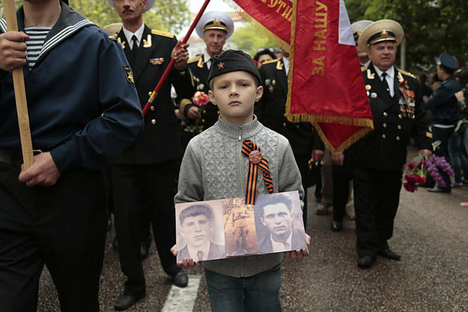 A boy wears a ribbon symbolizing the Soviet victory in WWII, and holds portraits of relatives who served in the Soviet Army, during a Victory Day military parade in Sevastopol, Crimea, Friday, May 9, 2014. Crimea, which hosts a major Russian Black Sea Fleet base, is also set to hold a massive navy parade in the port of Sevastopol, celebrating the Russian takeover. (AP Photo/Ivan Sekretarev)