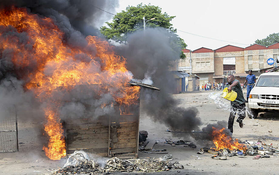 An opposition protester throws water to put out flames on a burning barricade set by him and others, when it started to burn overhead electricity cables providing power to the neighborhood, in the Buyenzi district of the capital Bujumbura, Burundi, Tuesday, May 26, 2015. Protests continued in the capital Tuesday, with demonstrators saying they will continue until President Pierre Nkurunziza steps down at the end of his second term. (AP Photo/Berthier Mugiraneza)