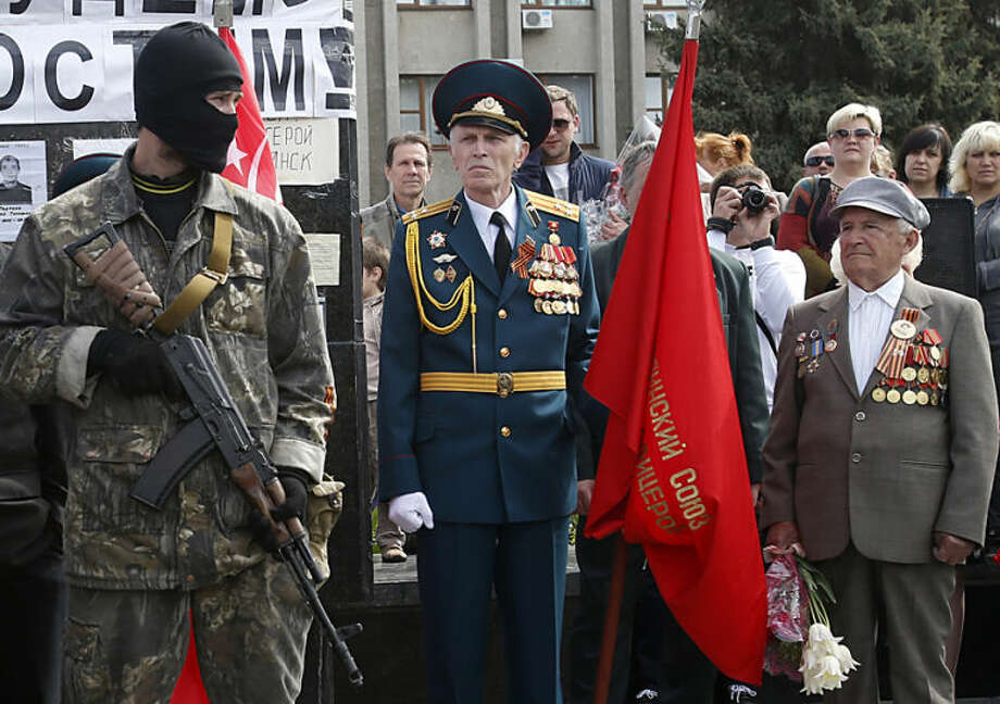 A pro-Russian gunman stands guard in front of World War II veterans, during a Victory Day celebration, which commemorates the 1945 defeat of Nazi Germany, in the center of Slovyansk, eastern Ukraine, Friday, May 9, 2014. Putin's surprise call on Wednesday for delaying the referendum in eastern Ukraine appeared to reflect Russia's desire to distance itself from the separatists as it bargains with the West over a settlement to the Ukrainian crisis. But insurgents in the Russian-speaking east defied Putin's call and said they would go ahead with the referendum. (AP Photo/Darko Vojinovic)