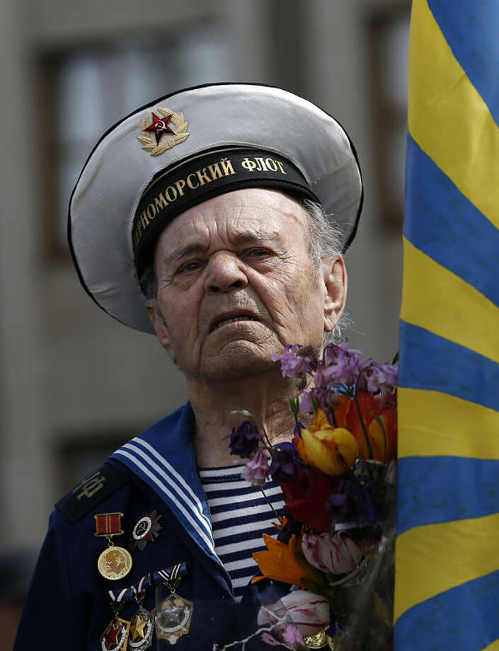 A World War II veteran attends a Victory Day celebration, which commemorates the 1945 defeat of Nazi Germany, in the center of Slovyansk, eastern Ukraine, Friday, May 9, 2014. Putin's surprise call on Wednesday for delaying the referendum in eastern Ukraine appeared to reflect Russia's desire to distance itself from the separatists as it bargains with the West over a settlement to the Ukrainian crisis. But insurgents in the Russian-speaking east defied Putin's call and said they would go ahead with the referendum. (AP Photo/Darko Vojinovic)