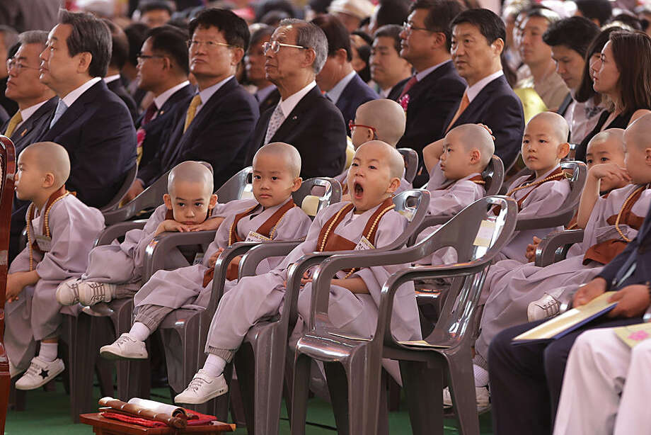 A shaven-headed young boy yawns during a special service to celebrate the 2,559th birthday of Buddha at the Chogye Temple in Seoul, Monday, May 25, 2015. Buddhists prayed for the unification between South and North Korea at the service. (AP Photo/Ahn Young-joon)