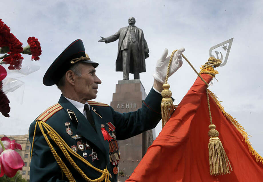 A former Soviet Union army veteran prepares a Soviet army flag as a symbol of victory, in front of the monument of Soviet revolutionary leader Vladimir Lenin, during a Victory Day celebration, which commemorates the 1945 defeat of Nazi Germany, in Kharkiv, Ukraine, Friday, May 9, 2014. Putin's surprise call on Wednesday for delaying the referendum in eastern Ukraine appeared to reflect Russia's desire to distance itself from the separatists as it bargains with the West over a settlement to the Ukrainian crisis. But insurgents in the Russian-speaking east defied Putin's call and said they would go ahead with the referendum. (AP Photo/Efrem Lukatsky)