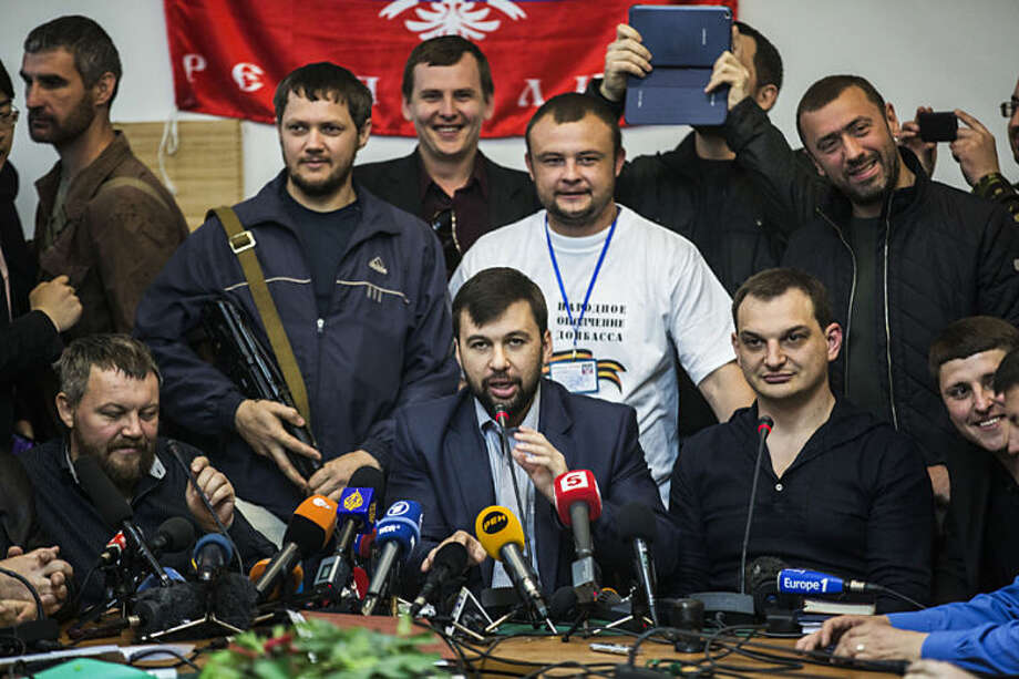 The head of the elections commission of the so-called Donetsk People's Republic, Denis Pushilin, center foreground, speaks at a news conference about the upcoming referendum, at the occupied administration building in Donetsk, Ukraine, Thursday, May 8, 2014. The pro-Russia insurgency in eastern Ukraine decided Thursday to go ahead with Sunday's referendum on autonomy despite a call from Russian President Vladimir Putin to delay it. (AP Photo/Manu Brabo)