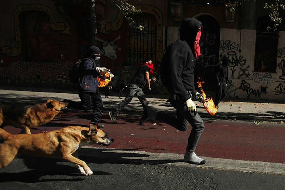 Protesters run forward as they prepare to throw petrol bombs towards police during violent clashes in Santiago, Chile, Thursday, May 8, 2014. Tens of thousands of students protested in Chile in a mostly peaceful protest that was marred at the end by violent clashes with police. This was first march demanding education reform since President Michelle Bachelet took power on promises of deep changes. (AP Photo/Luis Hidalgo)