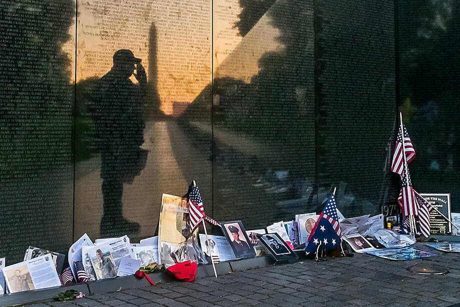 "Army veteran Bernie Klemanek, of Mineral, Va., stops to salute his fallen comrades on Memorial Day during an early morning visit to ""The Wall"" at the Vietnam War Memorial in Washington, Monday, May 25, 2015. (AP Photo/J. David Ake)"