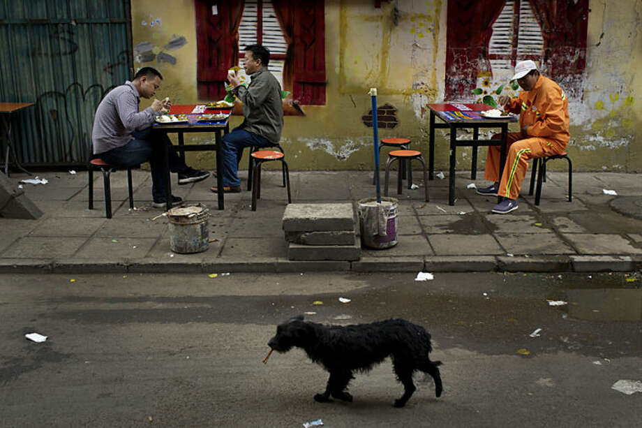 Men eat their lunches at a roadside food stall as a dog walks past with a leftover bone in mouth, in Beijing, Friday, May 9, 2014. China's inflation eased in April, giving the government more leeway if needed to stimulate the slowing economy. (AP Photo/Alexander F. Yuan)
