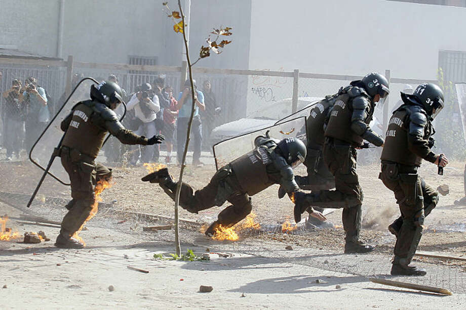 A Chilean riot police officer trips and falls down, as he and his fellow officers run away from flames from a petrol bomb thrown by protesters in violent clashes, during a student march in Santiago, Chile, Thursday, May 8, 2014. Tens of thousands of students protested in Chile in the first march demanding education reform since President Michelle Bachelet took power on promises of deep changes. (AP Photo / Luis Hidalgo)