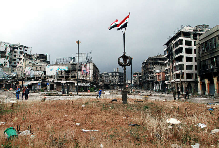 Two Syrian national flags hang on a pole as government officials inspect damages in the old city of Homs, Syria, Thursday, May 8, 2014. Hundreds of exhausted Syrian rebels withdrew Wednesday from their last remaining strongholds in the heart of Homs, surrendering to President Bashar Assad a bloodstained city that was once the center of the revolt against him. For Assad, it is a powerful victory ahead of presidential elections. For the rebels, the dramatic exit after two years of enduring grueling assaults and siege captures their sense of abandonment amid world reluctance to help shift the balance of power on the ground. (AP Photo)