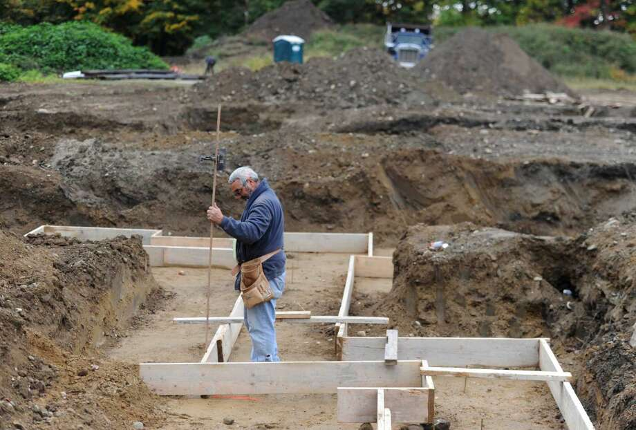 Carlos Rodrigues, of C-Rod Foundations, works on leveling the foundation at the construction site of the former Lexington Gardens in Newtown, Conn. Thursday, Oct. 2, 2014. The area is being developed into a commercial and office complex that town officials hope will become a village area destination for Newtown.