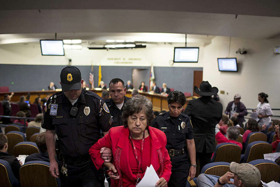Activist Nora Tachias-Anaya is escorted from a city council meeting in Albuquerque, N.M., Thursday, May 8, 2014. At least seven people were removed from the chambers and given a criminal trespass notice saying not to return to council chambers for 90 days. The Albuquerque City Council gathered Thursday under new rules and heightened security designed to avoid an angry confrontation like the one that broke out earlier in the week amid community outrage over a spate of deadly police shootings. (AP Photo/Juan Antonio Labreche)