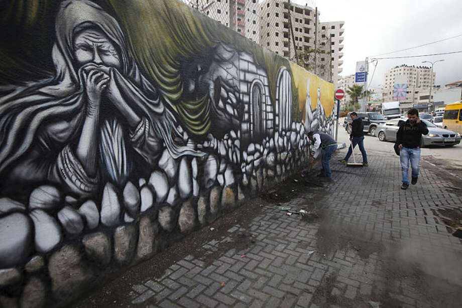 "Palestinians walk past a mural marking the 66th anniversary of Nakba Day in the Qalandia refugee camp near the West Bank city of Ramallah on Thursday, May 8, 2014. Palestinians annually mark ""nakba,"" or ""catastrophe,"" the term they use for May 15 to describe their defeat and displacement in the war that led to Israel's founding in 1948. (AP Photo/Majdi Mohammed)."