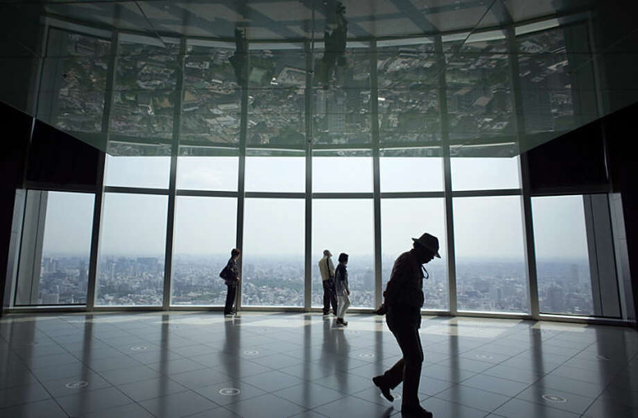 Tourists take in the views of Tokyo from the Roppongi Hills Mori Tower in Tokyo, Friday, May 9, 2014. (AP Photo/Eugene Hoshiko)