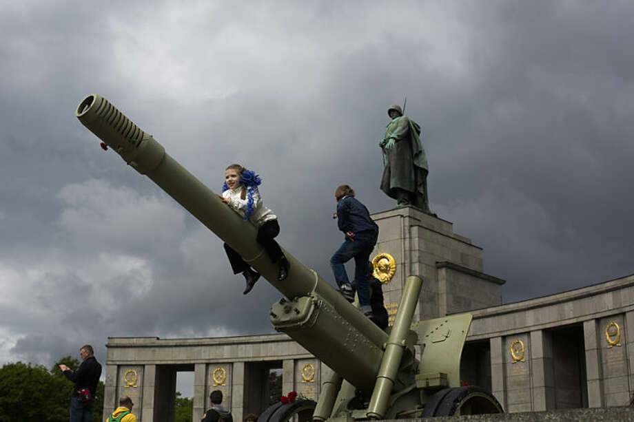 Russian girl Sophia plays with other children on an ordnance during the celebrations of Victory Day at the Soviet war monument and cemetery at the district Tiergarten in Berlin, Germany, Friday, May 9, 2014. Hundreds of Russians attend the celebration in the German capital to mark the victory over Nazi-Germany. (AP Photo/Markus Schreiber)