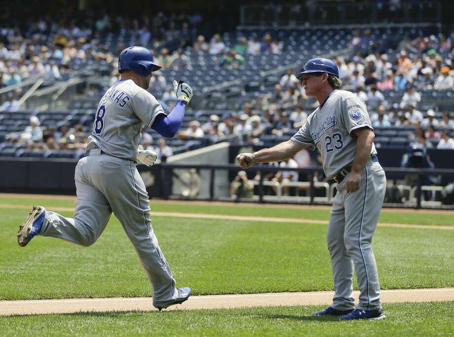 Kansas City Royals' Mike Moustakas (8) is greeted by third base coach Mike Jirschele (23) after hitting a solo home run against the New York Yankees during the first inning of a baseball game, Wednesday, May 27, 2015, in New York. (AP Photo/Julie Jacobson)