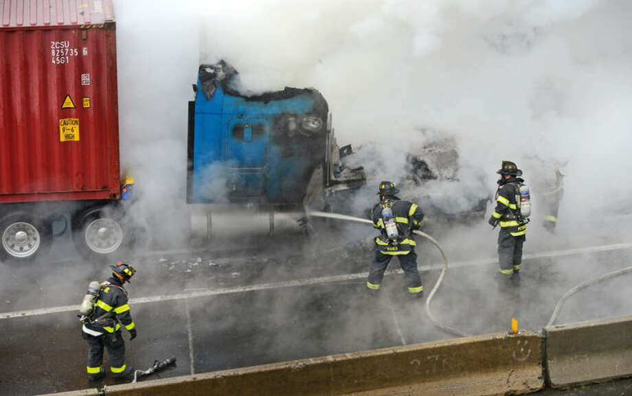 Hour photo / Erik Trautmann Norwalk firefighters fight a tractor trailer fire on I-95 Southbound at exit 14 Thursday morning