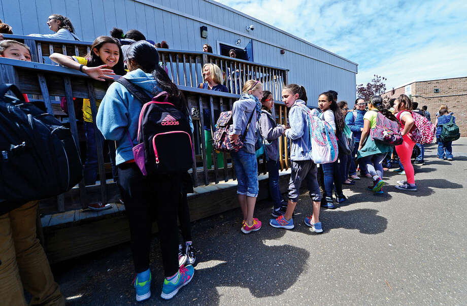 Jefferson Elementary School students exit portable classrooms Wednesday, May 18, 2016, at the school in Norwalk, Conn. Jefferson has one of the most crowded schools and has 10 classrooms in portables. The over-enrollment of Norwalk public schools has led to the use of portable school classrooms at many schools.
