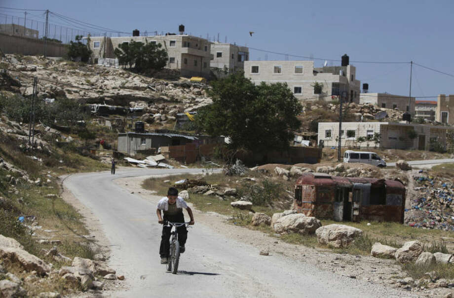 In this May 1, 2014 photo, a Palestinian bedouin rides a bike in Arab al Jahalin, east of Jerusalem. Leaders of the area's Jahalin tribe, rights activists and international aid officials believe the demolitions in Jabal al-Baba and eviction orders for another village are part of a push by Israel to relocate hundreds of Palestinian Bedouins and make way for Israeli settlements. (AP Photo/Majdi Mohammed)