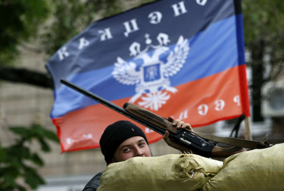A pro-Russian gunman stands behind the barricades and shows his hunting rifle in front of the flag of the self-proclaimed Donetsk People's Republic, in the center of Slovyansk, eastern Ukraine, Thursday, May 8, 2014. A strong majority of Ukrainians want their country to remain a single, unified state and this is true even in the largely Russian-speaking east where a pro-Russia insurgency has been fighting for autonomy, a poll released Thursday shows. (AP Photo/Darko Vojinovic)